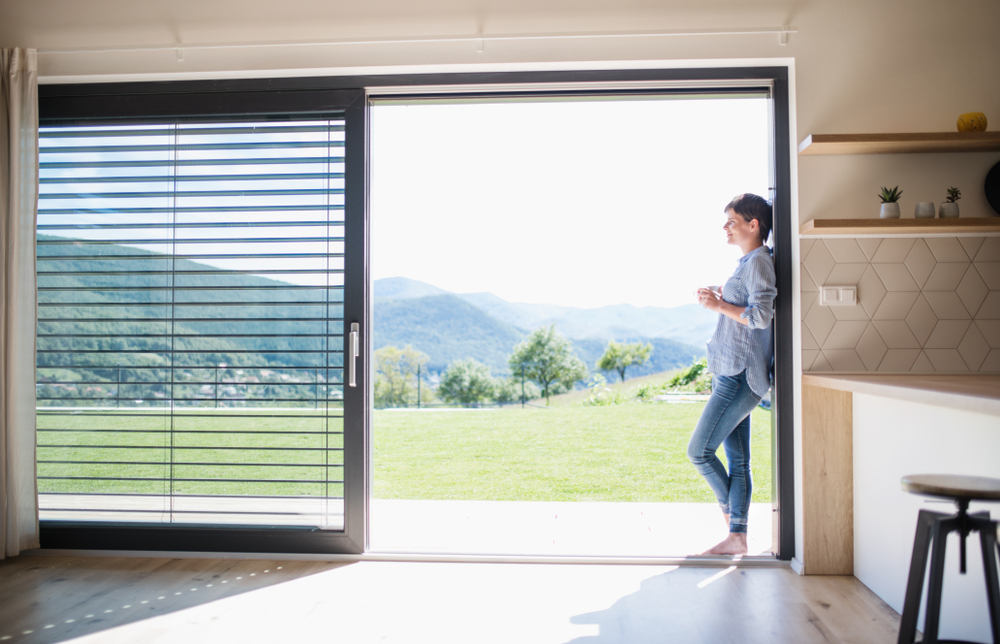 Side view of young woman with coffee standing by patio door at home
