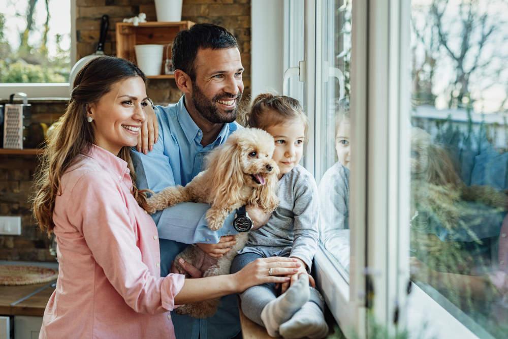Happy family looking through window (Homeowners Trust United Builders with Window & Door Replacement)